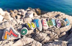Montenegro namn som göras av målade stenar på havsbakgrund Fotografering för Bildbyråer