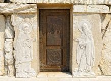 Door with a picture of biblical plots. Montenegro, Podgorica, elements of decor and architecture of the Cathedral of the Resurrection of Christ, a door with a Royalty Free Stock Image