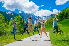 Tourists joyfully jump up against the background of snow-capped mountains. Royalty Free Stock Photos