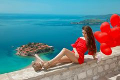 Montenegro. Romantic girl with heart balloons over famous Sveti. Stefan island in Budva. Happy brunette traveler in red dress sightseeing Adriatic Sea, Balkans stock image
