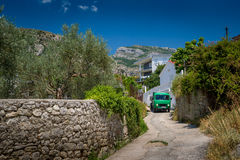 Montenegro rural road. Typical rural road in the village of Montenegro. Old cargo car is driving at summer sun heat Stock Image
