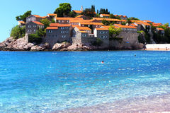 Montenegro`s a major tourist attraction - the island of Sveti Stefan, the blue crystal clear sea, people swim Stock Images