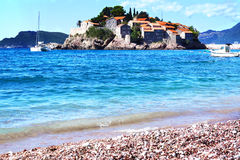Montenegro`s a major tourist attraction - the island of Sveti Stefan left the beach, the blue crystal clear sea, yachts Stock Images