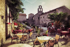 Montenegro, street cafe. Empty coffee terrace with tables and chairs in old town of Budva on sunny day at sunset, Montenegro. Filtered image, vintage effect Royalty Free Stock Photography