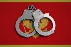 Montenegro vlag en politiehandcuffs Het concept naleving van de wet in het land en bescherming tegen misdaad stock afbeeldingen