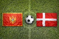 Montenegro vs. Denmark flags on soccer field Royalty Free Stock Images