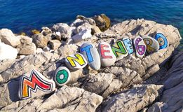 Montenegro word on the painted stones on the rocky beach, sea background Stock Photos