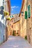 Montepulciano, Italia Vecchia via stretta nel centro della città con le facciate variopinte Immagini Stock Libere da Diritti