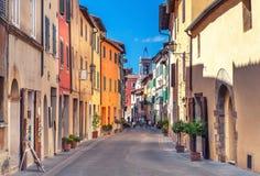 Montepulciano, Italien - 25. August 2013: Alte schmale Straße in der Mitte der Stadt mit bunten Fassaden Stockfotografie