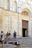 Street musicians on steps of Cathedral in tuscan town Montepulciano, Tuscany, Italy royalty free stock image