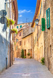 Montepulciano, Italy. Old narrow street in the center of town with colorful facades. Montepulciano, Italy. Old narrow street lined with stone blocks in the royalty free stock images