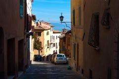 MONTEPULCIANO TUSCANY - OKTOBER 14, 2017: Gammal gata av Montepulciano med en vita Fiat 500 på en solig höstdag Fotografering för Bildbyråer