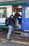 Monter dans le train avec la valise lourde Photo stock