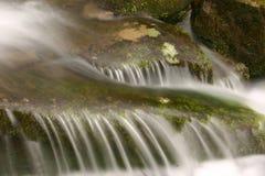 Monter en cascade au-dessus des roches Photographie stock libre de droits