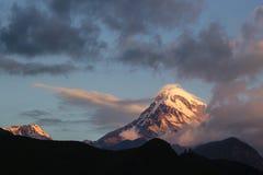 Montera den Kazbek och Gergeti Treenighetkyrkan i soluppgångljus Royaltyfria Bilder