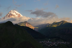 Montera den Kazbek och Gergeti Treenighetkyrkan i soluppgångljus Royaltyfri Bild