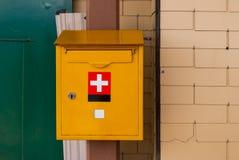 Monterade schweizisk postgång för den gula brevlådan på en tegelstenvägg royaltyfri bild