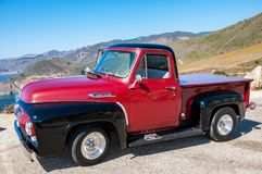 MONTEREY, CALIFORNIA - SEPTEMBER 10, 2015 - Bright red and black classic Ford F-100 parked on the shore of the Pacific ocean, on t royalty free stock photos