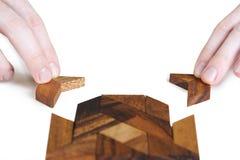 montering av händer bemannar fyrkantigt trä för pussel Arkivfoto