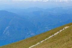 Montering Baldo, Italien - Augusti 15, 2017: gå bergturism folket klättrar berget Royaltyfri Fotografi