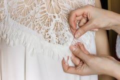 Montering för brud- kappa sömmerskan förbereder klänningen till monteringen royaltyfria bilder