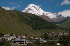 Montering Kazbek och Gergeti Trinitykyrka Royaltyfri Foto