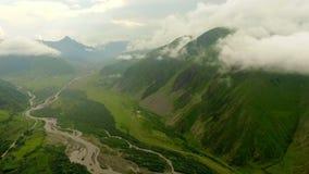 Montering Kazbek Sikt från ovannämnt på en grön bergdal och bergby lager videofilmer