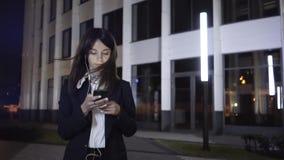 Montering van een jonge onderneemster met smartphone en hoofdtelefoons in een nachtstad stock video