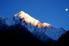 Monteringen tände vid strålarna av resningsolen Soluppgång i Himalayan mo Arkivfoton