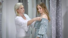 Monteringsklänning för ung dam, i att anpassa studion Kvinnlig couturie som arbetar på ny samling och försöker på den nya kappan  stock video