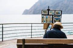 Monterosso Italien - April 8, 2016: Oidentifierad gatakonstnär som säljer hans souvenir för landskapmålning vid havet på Monteros Arkivfoto