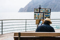 Monterosso, Italy - Apr 8, 2016: Unidentified street artist selling his landscape painting souvenirs by the ocean at Monterosso, C Stock Photo
