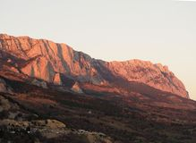 Montes da pedra calcária da montanha, iluminados pelo sol de ajuste com gaivotas abaixo Foto de Stock Royalty Free