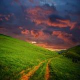 Montes e estrada às nuvens vermelhas Fotografia de Stock Royalty Free