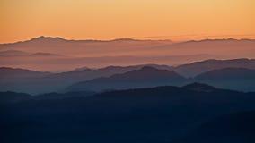 Montes no fundo do por do sol Imagens de Stock