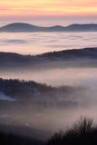 Montes sobre nuvens no por do sol fotografia de stock royalty free