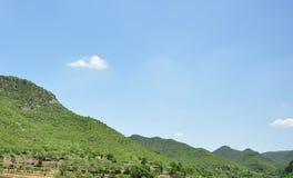 Montes verdes e céu azul no dia ensolarado Fotografia de Stock