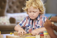 Montessori Pupil Working At Desk With Wooden Shapes Stock Photo
