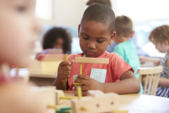 Montessori Pupil Working At Desk With Wooden Shapes Stock Images