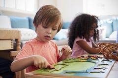 Montessori-Schüler, der am Schreibtisch mit hölzernen Formen arbeitet lizenzfreie stockbilder
