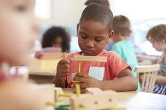 Montessori-Schüler, der am Schreibtisch mit hölzernen Formen arbeitet Stockbilder