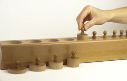 Montessori Wooden Cylinders with Hand Stock Photography