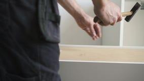 Monteur de meubles conduisant des clous dans des étagères clips vidéos