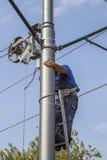 Monteurs de lignes installant le système d'alimentation d'offre de tram Photographie stock libre de droits
