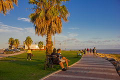 MONTEVIDEO, URUGUAY - 4 DE MAYO DE 2016: puesta del sol agradable en el becah, algunas personas gozando de la luz del sol y de un Imagen de archivo libre de regalías