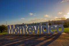 MONTEVIDEO, URUGUAY - 4. MAI 2016: Montevideos Zeichen beschädigte durch einige Graffitis mit der Stadt als Hintergrund lizenzfreies stockbild