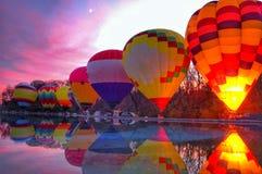 Montez en ballon la lueur au coucher du soleil près d'une piscine se reflétante au festival local Image libre de droits