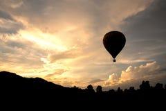 Montez en ballon le vol sur le ciel dans le style de silhouette de temps de soirée Photos stock