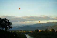 Montgolfières colorées volant au-dessus de la montagne images libres de droits