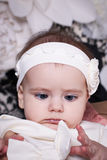 6 month baby girl in a white dress looks at the funny bow on dre. 6 month baby girl in white dress and white ribbon on his head, surprised looks on the bow on royalty free stock photos
